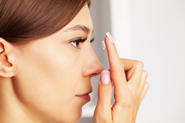 Довольно молодая женщина надевает контактные линзы для зрения