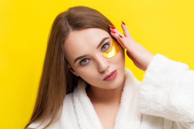 Pretty young woman puts patches under the eyes on a yellow