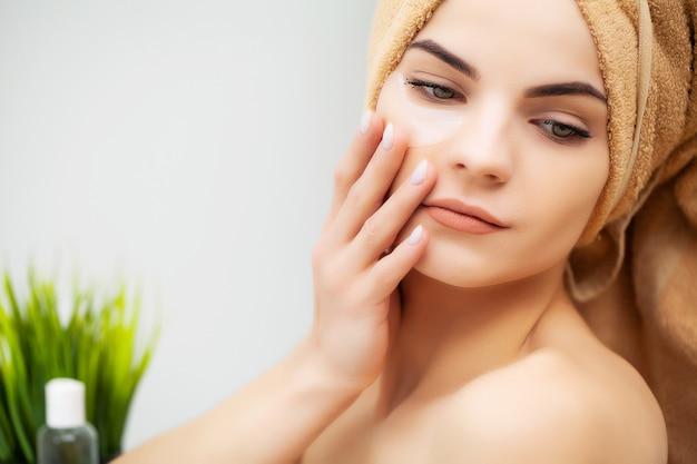 Довольно молодая женщина кладет пятна под глаза в ванной