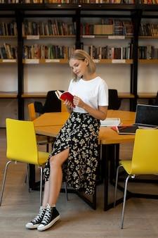 Довольно молодая женщина, читающая книгу