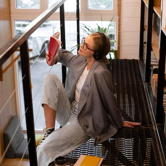 Довольно молодая женщина читает в библиотеке