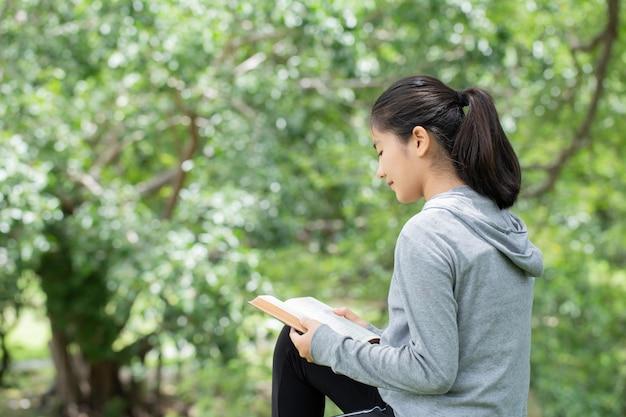 Довольно молодая женщина, читая библию в парке. читая книгу. концепция библии бога основана на вере и духовности.