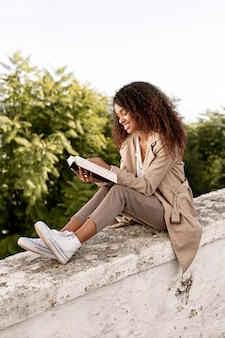 Pretty young woman reading a book outdoors