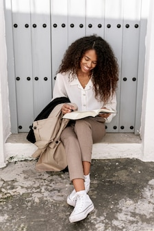 Pretty young woman reading a book outside