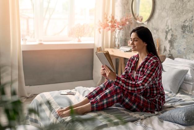 Giovane donna graziosa che legge un libro
