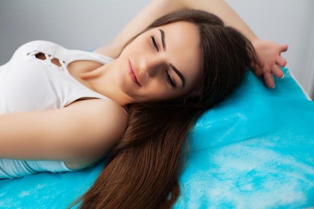 Довольно молодая женщина получает лазерное удаление волос на ногах в салоне красоты