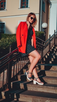 Pretty young woman in red jacket and dress on city street urban surface. old town. vertical photo