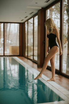 Pretty young woman relaxing by swimming pool