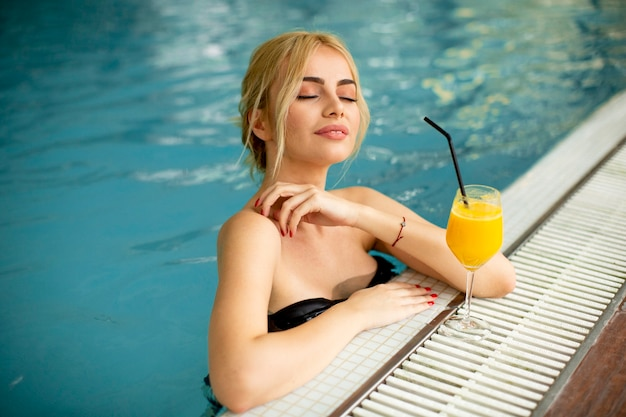 Pretty young woman relaxing on the interior swimming pool poolside