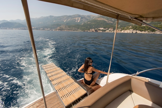 Pretty young woman relaxing on the yacht on sea at sunny day