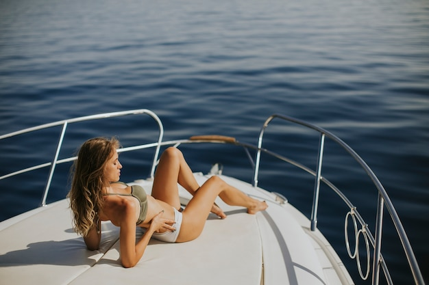 Pretty young woman relaxing on the yacht at sea