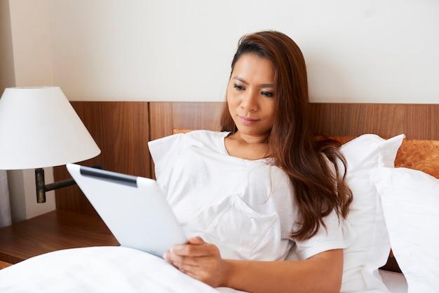 Довольно молодая женщина отдыхает в удобной кровати и читает увлекательную электронную книгу