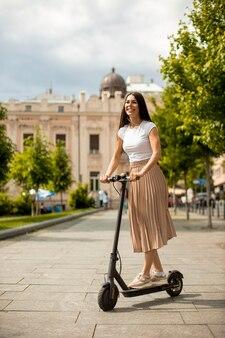 Довольно молодая женщина, едущая на электросамокате на улице