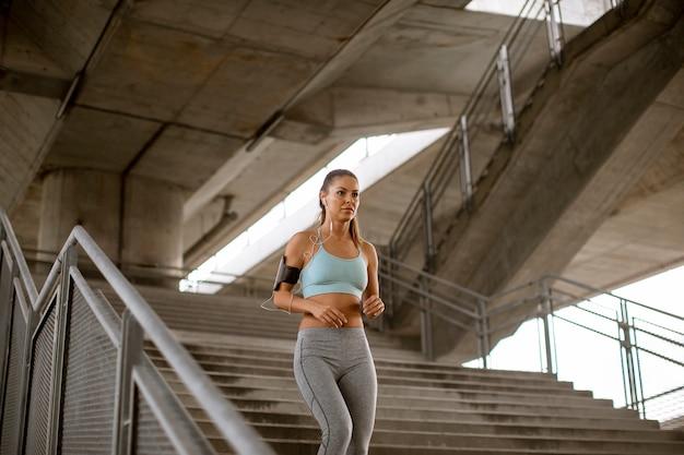 都市環境で階段を駆け下りるかなり若い女性