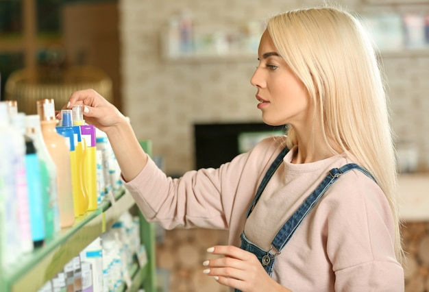 Pretty young woman selecting animal shampoo in pet shop