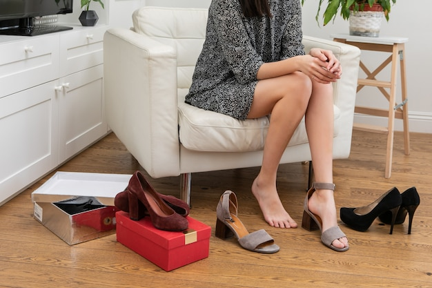 A pretty young woman in a short dress sits in a chair in the living room near the wardrobe and chooses a pair of shoes to wear today. a girl tries on high-heeled shoes. concept of online web shopping