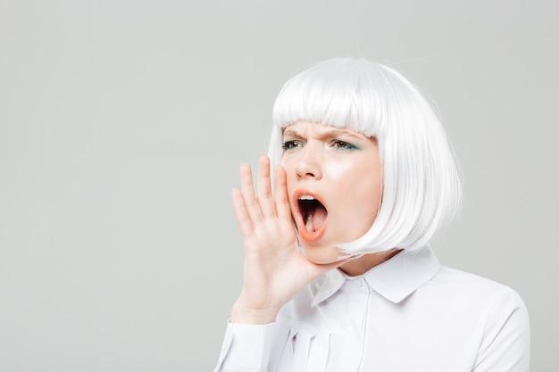Довольно молодая женщина кричит и зовет кого-то