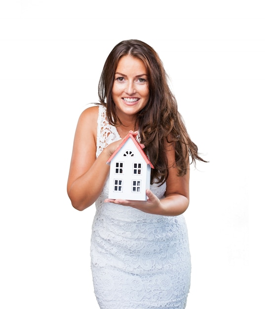 Pretty young woman showing a house object
