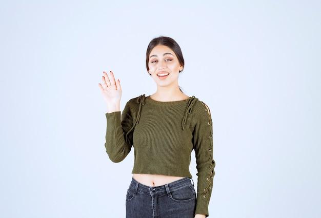 白い壁に顔を見せているかなり若い女性