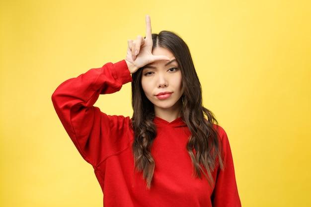 Довольно молодая женщина показывает жест рукой проигравшего