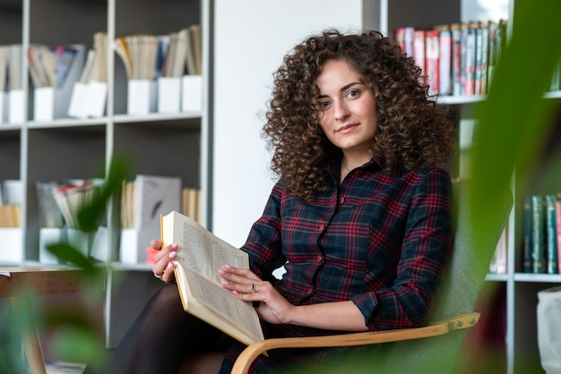 Pretty young woman sits  in the chair and  holds book, looking at the camera. open book lying on the knee- image