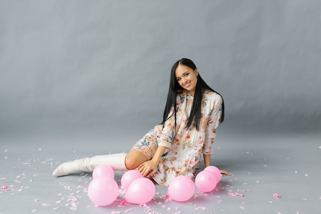 A pretty young woman sits near pink balloons and confetti on a gray studio backdrop.