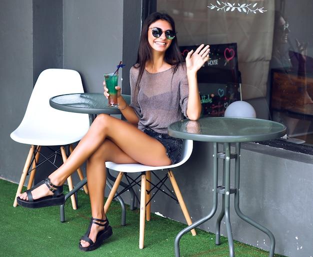 かなり若い女性がストリートシティカフェで一人で座って、夏のミニマルなヒップスターの外観、カクテルを飲み、ウェイターを求めます。