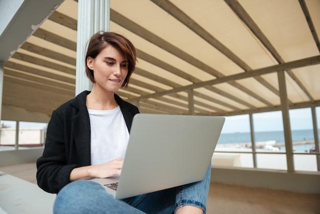Довольно молодая женщина сидит и использует ноутбук на террасе на пляже
