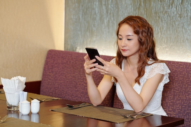 Довольно молодая женщина сидит за столиком в ресторане, пишет друзьям или проверяет социальные сети