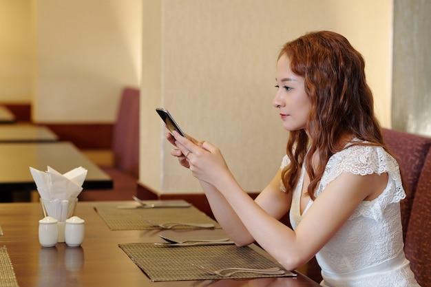 Довольно молодая женщина сидит за столом в ресторане, проверяет свой смартфон и отвечает на текстовые сообщения