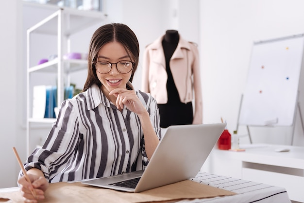 Довольно молодая женщина, сидящая за столом, используя свой ноутбук и делая заметки на выкройках одежды своим карандашом.
