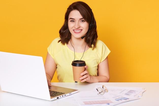ノートパソコンの前の白い机に座って、使い捨てカップからテイクアウトのコーヒーを飲むかなり若い女性