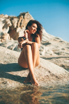 Pretty young woman sitting on the beach