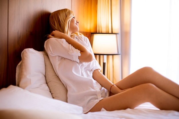 Pretty young woman sitting on the bed at room