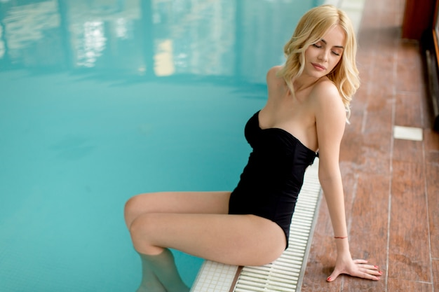 Pretty young woman sitting by the swimming pool