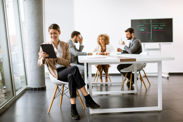 Pretty young woman sitting by the table with digital tablet in modern office in front of her team