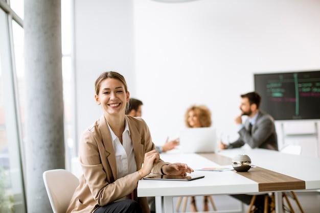 Довольно молодая женщина сидит за столом с цифровым планшетом и бумажной диаграммой в современном офисе перед своей командой