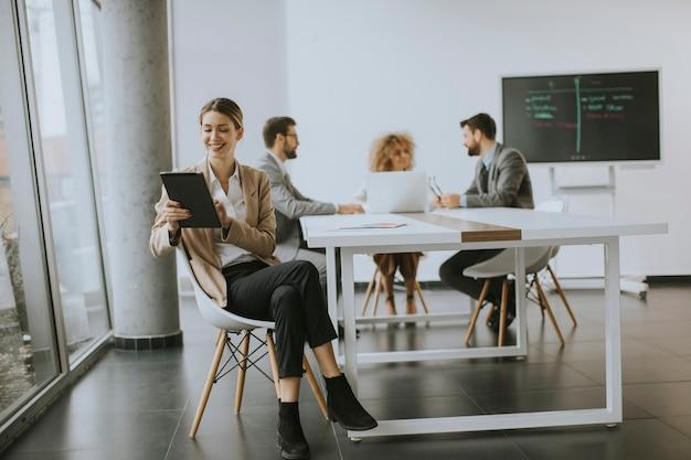 Довольно молодая женщина сидит за столом с цифровым планшетом в современном офисе перед своей командой