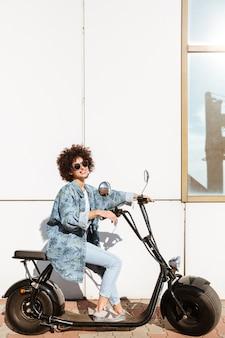 Pretty young woman sitting on a modern motorbike