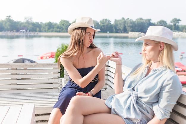ピンクの指を鳴らしているベンチに座っているかなり若い女性