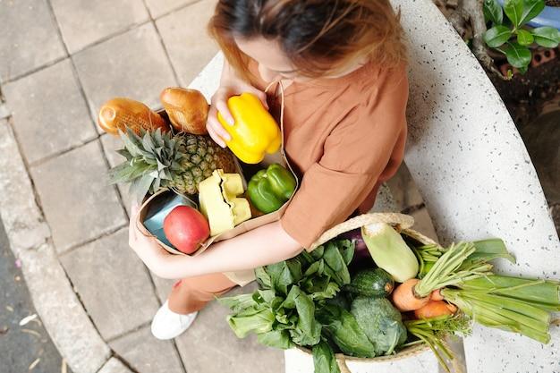 Довольно молодая женщина сидит на скамейке с двумя большими мешками свежих овощей, фруктов и хлеба