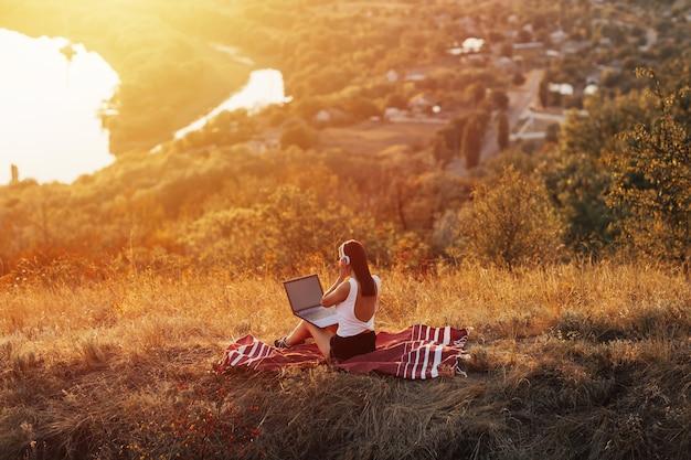Довольно молодая женщина, сидя на зеленой траве на холме в солнечный летний день.