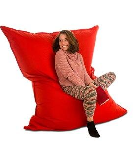 居間や他の部屋の赤いお手玉のソファの椅子に座って、白で隔離の本を持っているかなり若い女性