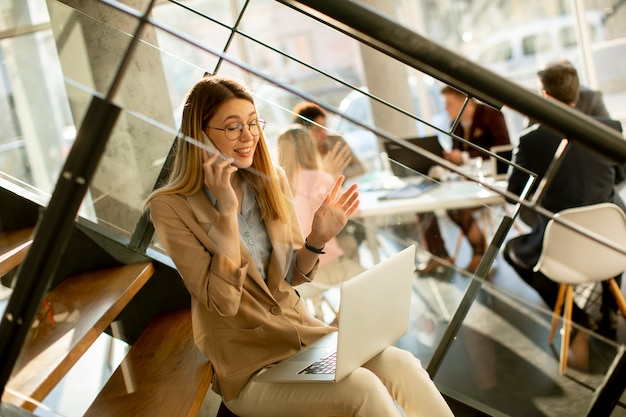 Довольно молодая женщина, сидящая на лестнице с ноутбуком и использующая мобильный телефон в современном офисе перед своей командой