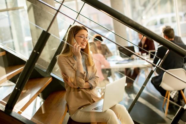 Довольно молодая женщина сидит на лестнице с ноутбуком и использует мобильный телефон в современном офисе перед своей командой