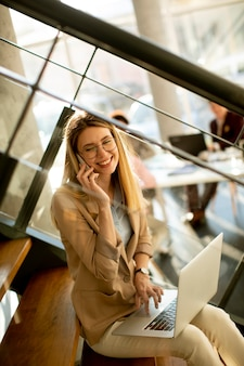 Pretty young woman sitting on the stairs with laptop and using mobile phone in modern office in front of her team