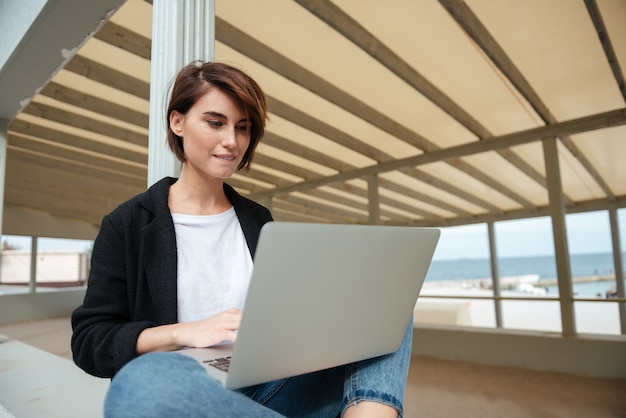 Pretty young woman sitting and using laptop on terrace on the beach