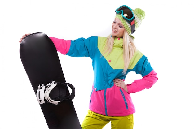 Pretty young woman in ski outfit and ski glasses hold snowboard