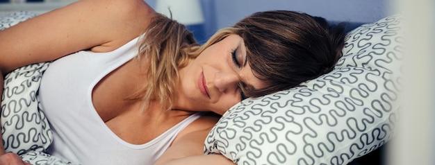 침대에서 평화롭게 자는 예쁜 젊은 여자