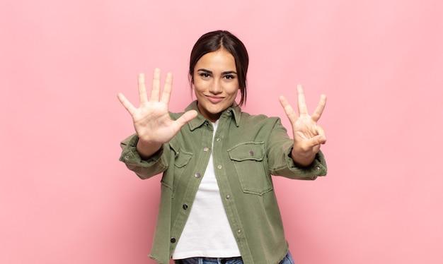 笑顔でフレンドリーに見えるかなり若い女性、前に手を前に8番または8番を示し、カウントダウン